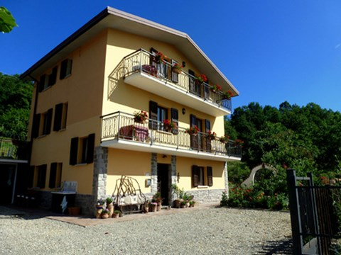 Casa Appennino, yellow three story chalet style house, with balconies
